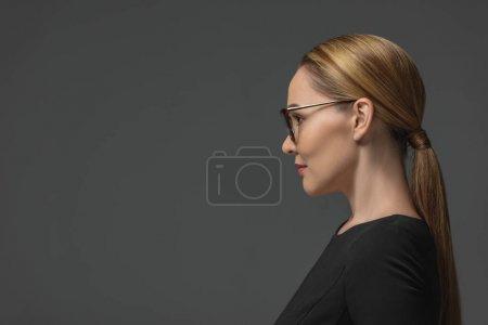 profile portrait of beautiful kazakh woman in eyeglasses looking away isolated on grey