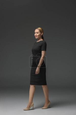 full length view of beautiful kazakh woman in black dress walking and looking away on grey