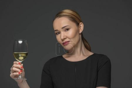 smiling kazakh woman holding glass of wine and looking at camera isolated on grey