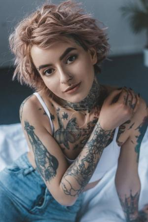 Photo for Portrait of tender tattooed girl with pink hair in bedroom - Royalty Free Image
