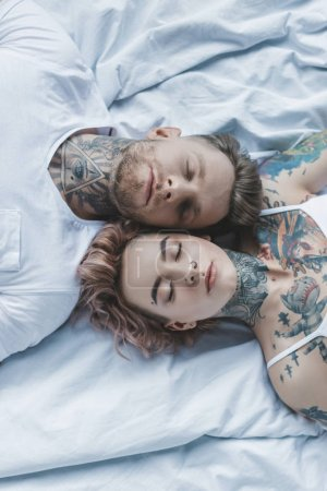 Photo for Top view of beautiful tattooed couple lying with closed eyes on white bed - Royalty Free Image