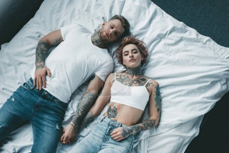 top view of young tattooed couple holding hands and lying on bed