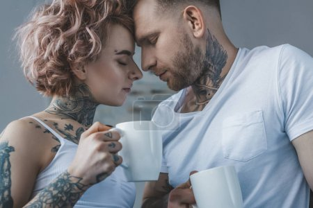 young tender tattooed couple with coffee touching foreheads at morning