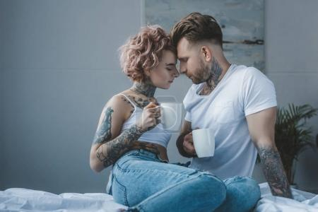 tender tattooed couple with coffee touching foreheads in bedroom at morning