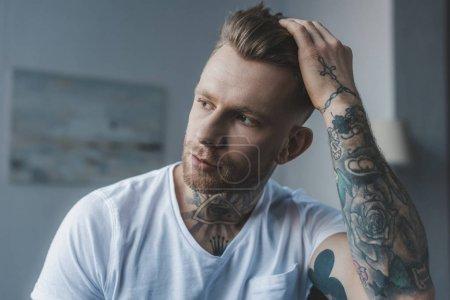 Photo pour Bel homme tatoué élégant, toucher ses cheveux - image libre de droit