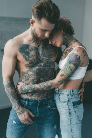 stylish tattooed lovers embracing in bedroom