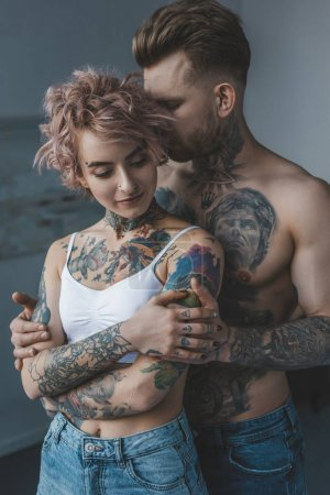 tender tattooed couple embracing in bedroom at home