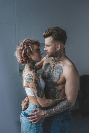 young tattooed couple embracing in bedroom