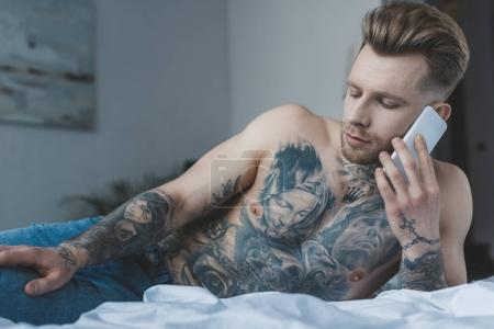 handsome shirtless tattooed man talking on smartphone while lying on bed