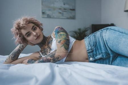 beautiful inked girl with pink hair lying on bed and looking at camera