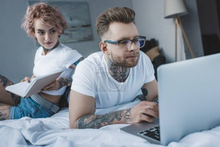 tattooed couple reading book and using laptop in bed