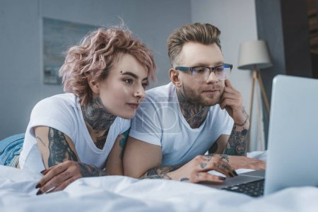 Photo for Young tattooed couple using laptop on bed in bedroom - Royalty Free Image