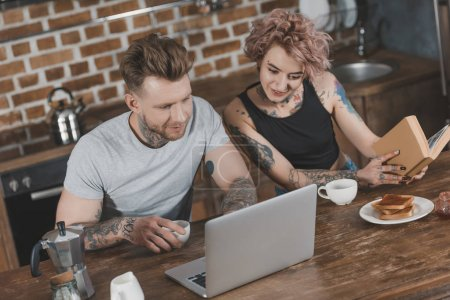 young couple using laptop and reading book during breakfast in kitchen