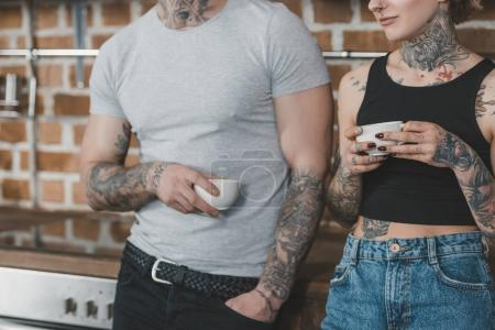 cropped view of tattooed couple drinking coffee in kitchen at morning
