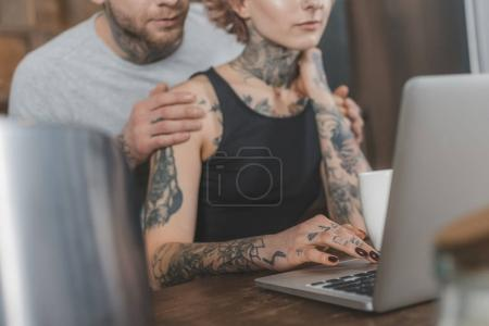 Photo for Cropped view of tattooed couple using laptop at home - Royalty Free Image