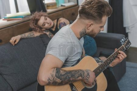 boyfriend playing on acoustic guitar for his girlfriend at home