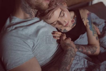 beautiful tattooed girl sleeping on her boyfriend at home