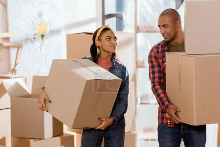african american couple holding cardboard boxes and moving to new apartment