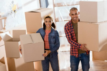 Photo for Beautiful african american couple holding cardboard boxes and moving to new home - Royalty Free Image