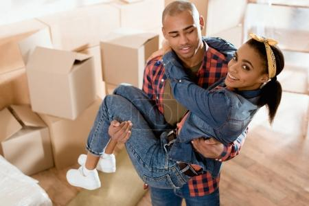 Photo for African american boyfriend holding on hands his girlfriend in new apartment with cardboard boxes - Royalty Free Image