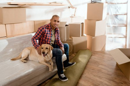 african american man with labrador dog in new apartment with cardboard boxes