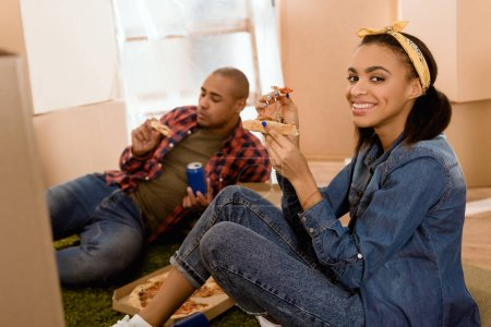Photo for African american couple eating pizza in new apartment with cardboard boxes - Royalty Free Image