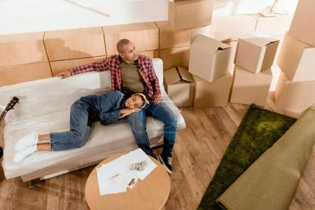 african american couple resting in new apartment with cardboard boxes