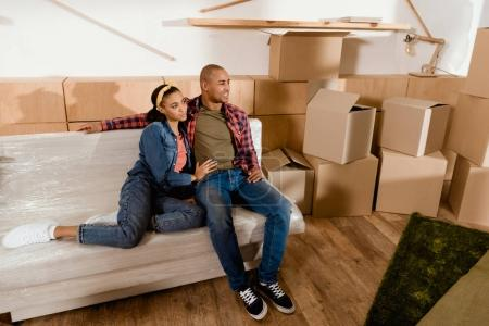 dreamy african american couple in new apartment with cardboard boxes