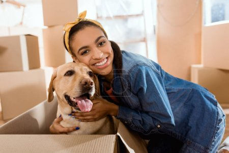 smiling african american woman with labrador dog in cardboard box