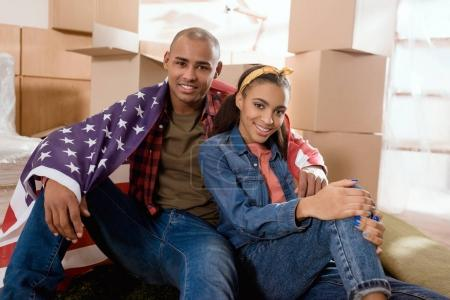 african american couple with united states flag sitting on floor at new home with cardboard boxes