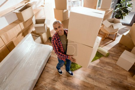 Photo for Young african american man holding cardboard box and moving into new home - Royalty Free Image