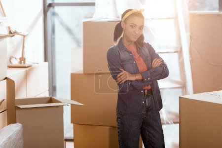 Photo for Attractive african american girl posing in new home with cardboard boxes - Royalty Free Image