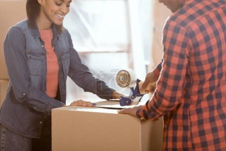 happy african american couple packing cardboard box to move in new home