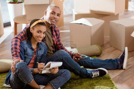 Photo for Smiling african american couple with smartphone and notepad sitting in new apartment - Royalty Free Image