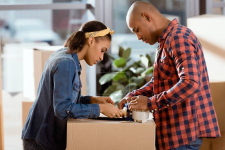 african american couple packing cardboard box with scotch tape