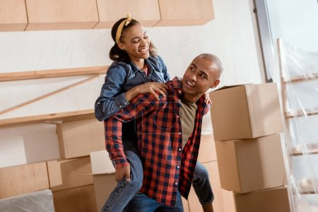 Photo for Happy african american couple piggybacking in new apartment with cardboard boxes - Royalty Free Image