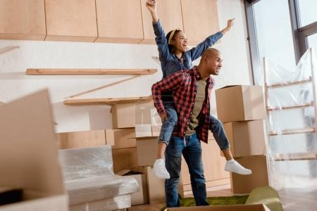 Photo for Excited african american couple piggybacking in new apartment with cardboard boxes - Royalty Free Image