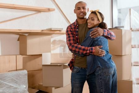 Photo for Happy african american couple hugging in new apartment with cardboard boxes - Royalty Free Image