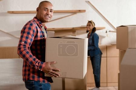 Photo for Happy african american couple holding cardboard box and moving to new apartment - Royalty Free Image