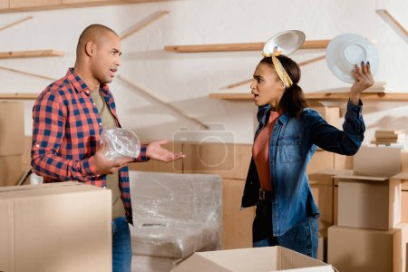 Photo for African american couple unpacking and quarreling in new apartment with cardboard boxes - Royalty Free Image