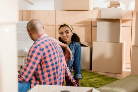 Photo for Dreamy african american couple in new apartment with cardboard boxes - Royalty Free Image