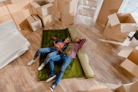 top view of dreamy african american couple lying on floor in new home with cardboard boxes