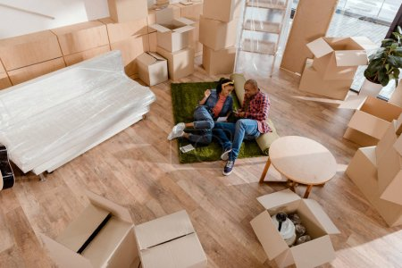 happy african american couple in new apartment with cardboard boxes