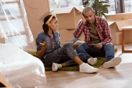 african american couple calculating budget in new apartment