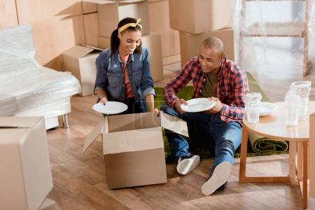 Photo for Happy young african american couple unpacking dishware in new apartment - Royalty Free Image