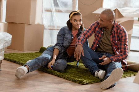 african american couple sitting on floor in new apartment with cardboard boxes