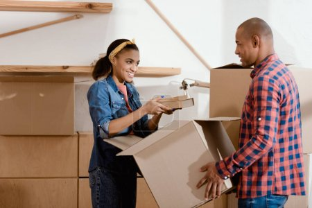 Photo for Happy african american couple unpacking books in new home - Royalty Free Image