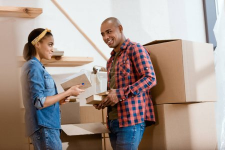 Photo for Smiling african american couple unpacking books in new home - Royalty Free Image