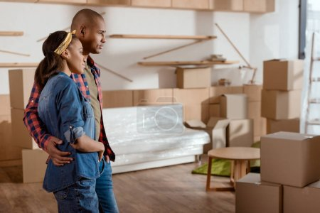 african american couple looking at new home with cardboard boxes