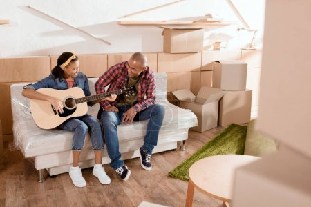 Photo for African american couple playing on acoustic guitar in new home with cardboard boxes - Royalty Free Image